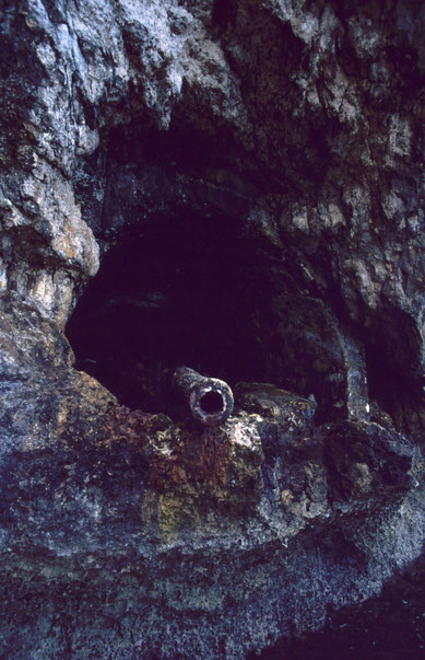 A Japanese defensive coastal gun, its rusted barrel peering from a sea-level cave in Palau.  It was one of many intended to protect the city of Koror and its harbor complex.