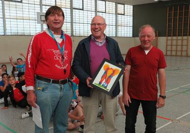 """Wolf-Rüdiger Umbach mit dem Bild eines Elefanten, der Fußball spielt. Dirk Kinne (rechts) und Manfred Wille hatten es ihm als Dank für das """"Daumendrücken"""" bei vielen sozialsportlichen Aktionen überreicht."""