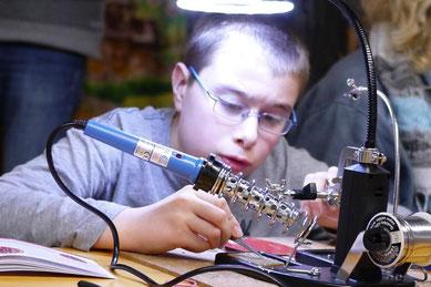 konzentrierter Junge beim Löten