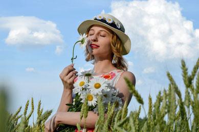 Junge Frau riecht an einer Margeritte