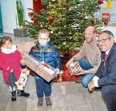 Filialleiter Andreas Palioudakis (r.) und der DRK-Vorsitzende Matthias Lahann verteilen die Geschenke an Finja und Neo.