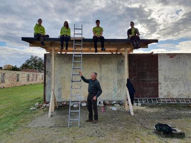 Sophie, Alexandra, Ulrich und Bennet (von links) auf dem Notdach sitzend. Unten stehend: Architekt Detlef Cordes. Foto: A. Ehresmann, 22.10.2020