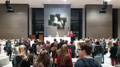 Landtagspräsidentin Dr. Gabriele Andretta vor den Jugendlichen und Begleitpersonen im Plenarsaal des Landtagsgebäudes