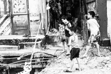 Picture in black and white: kids playing at throwing stones