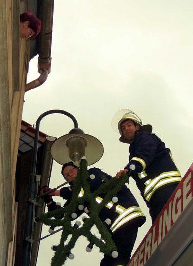 Zwei Feuerwehrler beim Anbringen der Weihnachtssterne. Beobachter gab es an diesem Tage viele.