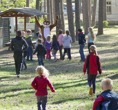 Der Osterhase war gekommen und winkte die Kinder zu sich.