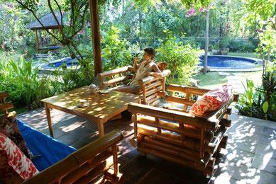 Veranda mit Bambusmoebeln, hinter dem Garten mit Pool ueppiger Bambus