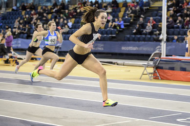 Heather Paton winning the 60H in record time, photo by Bobby Gavin