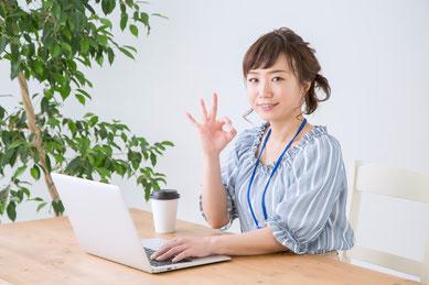 パソコンを前にして、右手でOKサインの女性