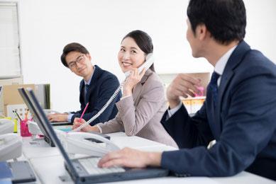 オフィスで、パソコンを使って仕事をしている男女3人