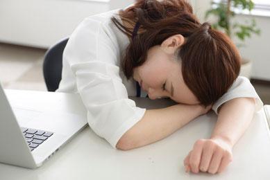 パソコンの前で突っ伏して寝ている女性