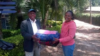 Mr. Mutugi überreicht Susan die 2 Woll-Zudecken...