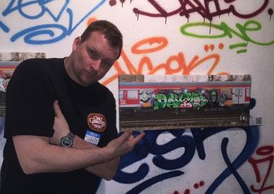 Oliver Nebel vor Graffitiwand