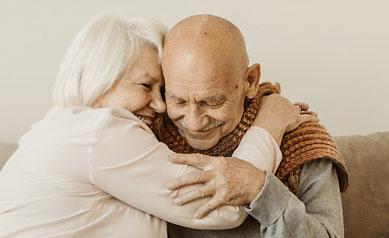 Älteres Paar auf Sofa in vertrauter Umarmung, lachend