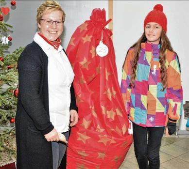 Filialleiterin Jana Panten (l.) freute sich mit der elfjährigen Adenisa aus Albanien über den hier noch verpackten Weihnachtsbaum.