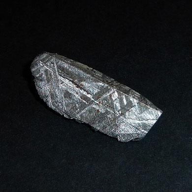 Ein kleines Stück des Gibeon-Eisen-Meteoriten (ca. 2,5 cm lang) mit schönen Widmanstätten-Strukturen und Neumannschen Linien
