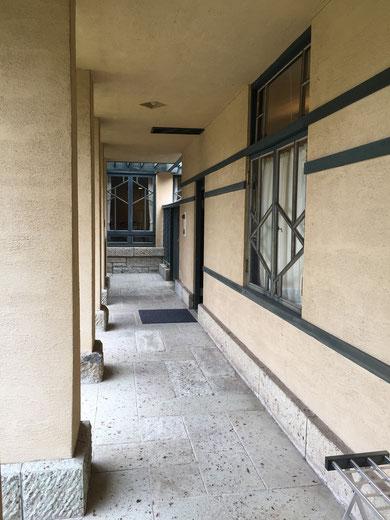 回廊の柱と緑に縁取られた壁。窓のデザインも一つ一つ違う。