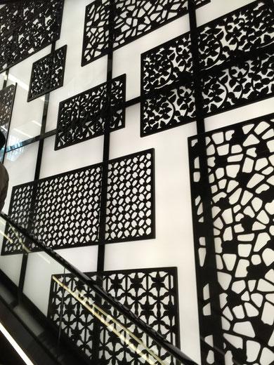 グランフロント内にあるエスカレーターのすぐ脇にある壁。アイアン?のデザインパネルが照明の上にある。暗くなるともっと素敵かな?