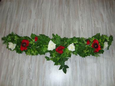 Kurze Girlande mit roten Mohnblumen und weißen Rosen.