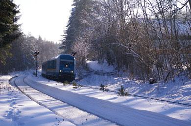 Ein Dieselzug mit Wagen aller Schattierungen kommt