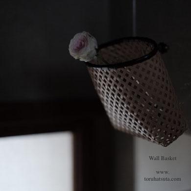 壁の籠に一輪のバラを