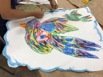 Een meisje knipt de randen van haar schilderij laangs een blauwe wolkenrand af. Op de wolk is een bontgekleurde vogel geschilderd in de kleuren geel, blauw, rrood en groen. Daarnaast is nog een kleinere vogel te zien. De vogel heeft een oranje snavel.
