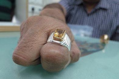 自身に合った宝石の処方をするインド人男性