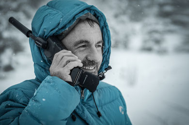 A man using a satalight phone in the mounatins
