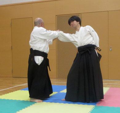 ④右足から踏み替えて転換 左手は丹田に結ぶ    以上、片手取り転換鏡返し
