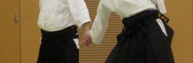 ④前方の右足先を後方に置き換えて小手を丹田で握る 右手は陰で一旦腰に結び