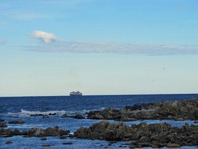 Weit draußen fährt ein Schiff der Hurtigrute vorbei