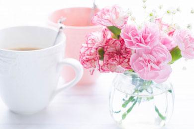 コーヒーの入った白とピンクのマグカップが2つ並んでいる。ピンクのカーネーションが活けられたガラスの花びん。