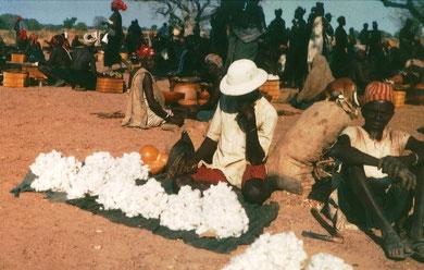 Auf einem Markt bietet ein Bauer seine Baumwolle feil