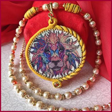 """Anhänger aus gelber Modelliermasse mit goldigen Glitzerpartikeln, mit Glückssymbol """"Löwe"""" und écru Perlenkette mit roten Swarovski-Kristallen écru P"""