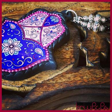 """Pendente realizzato con pasta modellante, mano di Fatima, con decorazioni floreali e simbolo """"OM"""""""