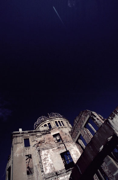 As if to symbolize the bombing strike that opened the nuclear age, a single contrail marks the sky above the Hiroshima Prefectural Industrial Promotion Hall (the 'Hiroshima Dome').