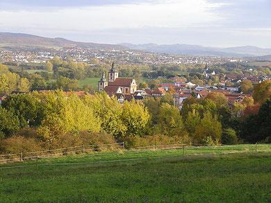 Im Vordergrund der Ortskern von Burghaun mit den beiden Kirchen, im Hintergrund Hünhan und Hünfeld
