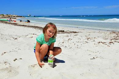 Lina beim Sand sammeln