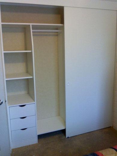 Closet con cajonera, repisas y barras de colgar ropa. Puertas correderas