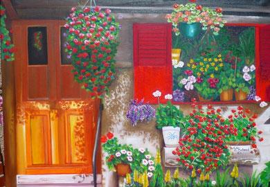 façade ensoleillée,  d'une maison aux volets rouges, recouverte de fleurs de toutes les couleurs