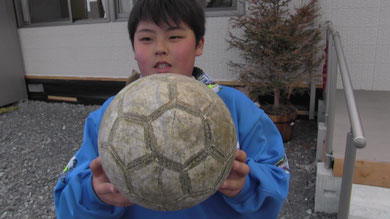 宝物のサッカーボールを手に、インタビューに答える少年、この時のインタビューをもとに 「帰ってきたサッカーボール」を創作。