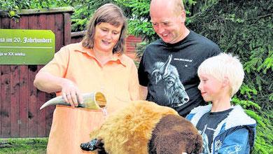 Kathrin Räsch tauft mit dem Wisentexperten Dirk Weichbrodt und dessen Sohn Gero (10) stellvertretend für Usina einen kleinen Plüschwisent. Foto: dp