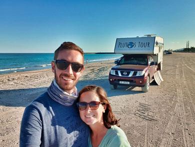 Schweizer Reiseblogger auf einem Sandstrand in den Vereinigten Arabischen Emiraten. Im Hintergrund das Wohnmobil und das Meer.