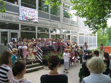 Kinder begrüßen Eltern und Besucher mit fröhlichen Liedern beim Schulfest