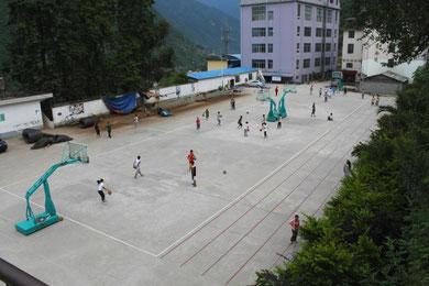 Der Schulhof. Im Hintergrund ist das Schulkiosk (blaues Dach) und daneben die große Kantine.