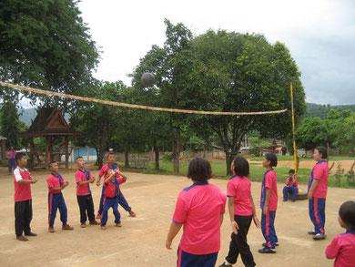 Mädchen und Jungen pritschen den Ball über das Netz