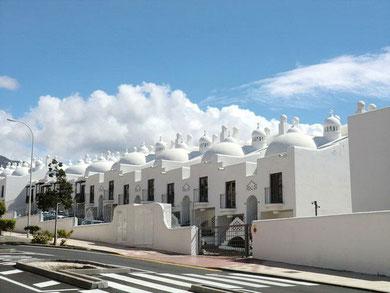 Straßenansicht von der Wohnanalge ganz in weiß.
