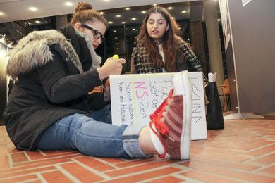 Nach der Preisverleihung setzen Ülkü Kahraman und Serivan Bagari ein Zeichen: sie beschriften einen der Papphocker, mit denen in der Ausstellung um Statements gegen Rechtsextremismus und Menschenfeindlichkeit gebeten wird.