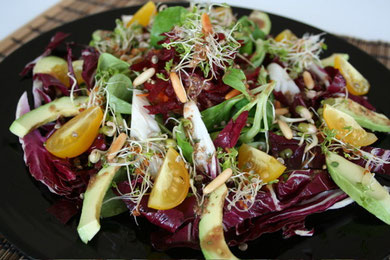 Field salad and radicchio with avocado, sprouts and yellow cherry tomatoes