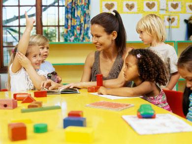 Lehrerin mit Kindern mit Bausteinen